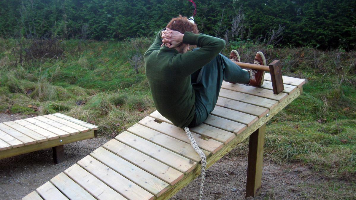 Skogsmulle visar hur du kan göra situps i Brösarps nya utegym.