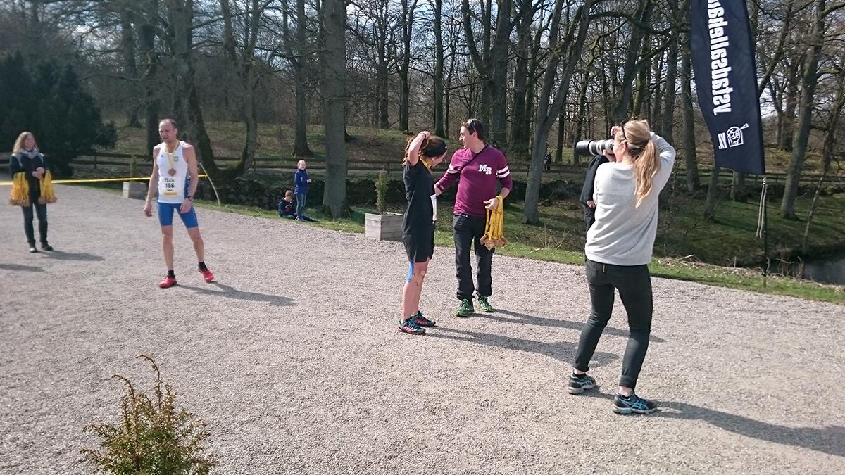 """Yoie """" Rastarunner"""" fotas av Runner's World och får trämedalj av arrangören och initiativtagaren Gaël Joly, medan dagens snabbaste på 12 km, Jens Persson, pustar ut. Foto: Fabian Rimfors"""